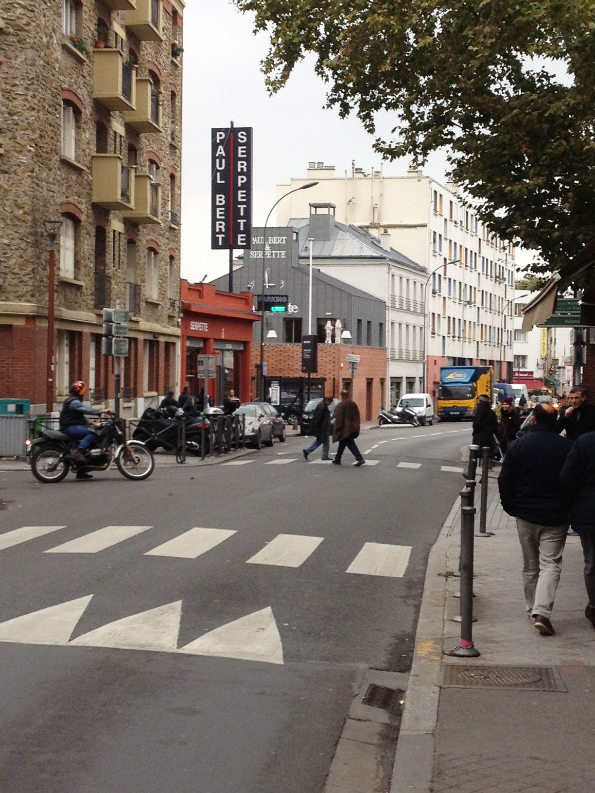 The view looking west on rue des Rosiers showing the Marché Paul Bert and Serpette