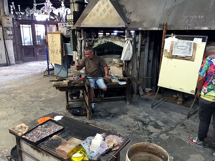 The glassblower is using tongs to shape a bowl